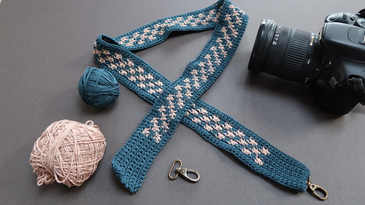 Grey background with a DSLR camera, two metal latch fitttings and two balls of linen yarn.  A crocheted camera strap in teh middle made up of dark teal and light dusky pink linen yarn.