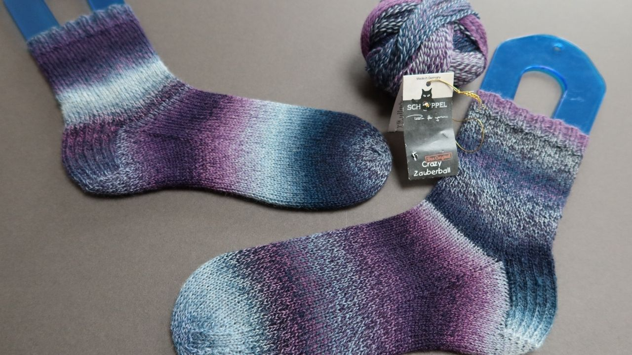 Grey background with fading knitted socks in teals, blues and plummy purples.