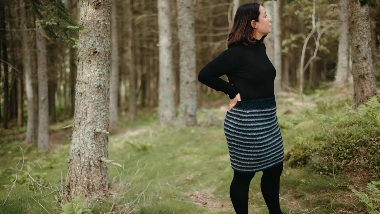 Pine forest in Scotland with a female model e=wearing balck tights and top and a blue striped Laminaria crocheted skirt.