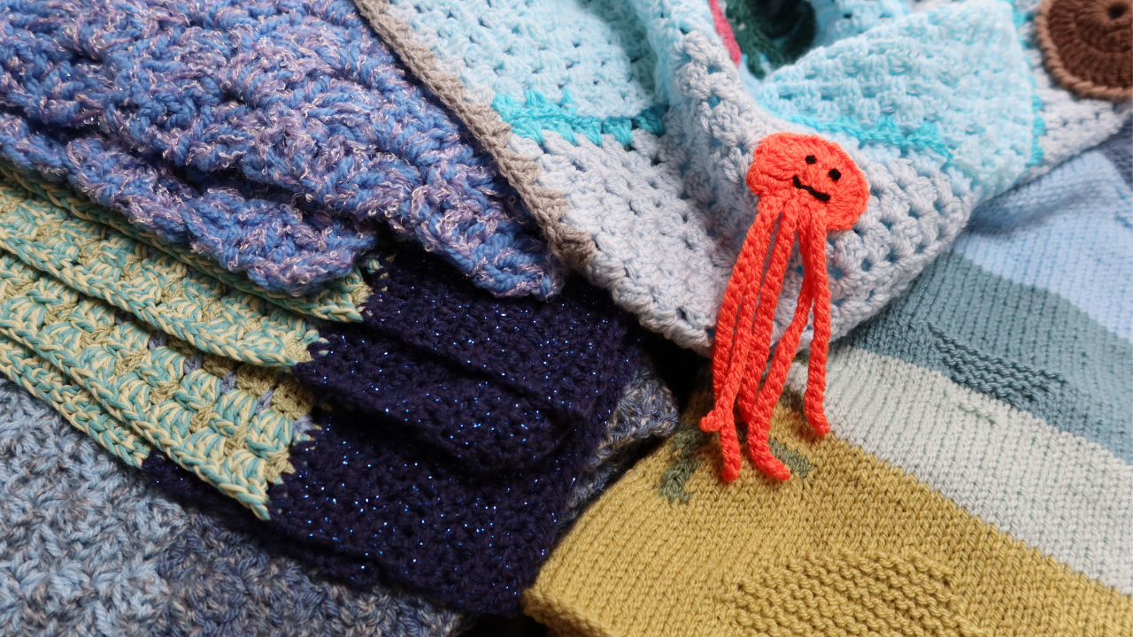 A big pile of crocheted and knitted panels all in blues and greens.  At the top of the pile is a crocheted blanket with an orange jellyfish embelishment.