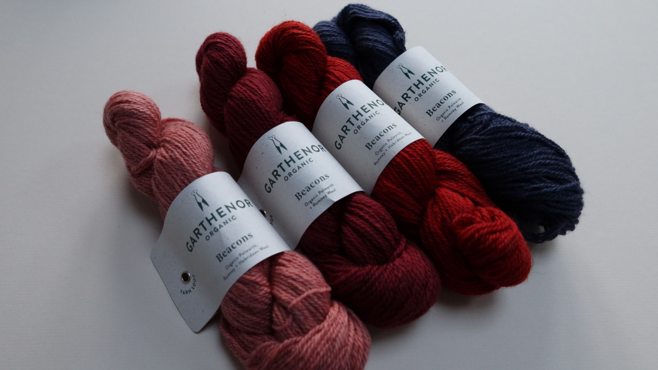 Four skeins of wool lying diagonally with white Garthenor ball bands.  They are all solid colours going from a dirty peachy pink, to a mid claret, to a brown tomato red and a French navy.