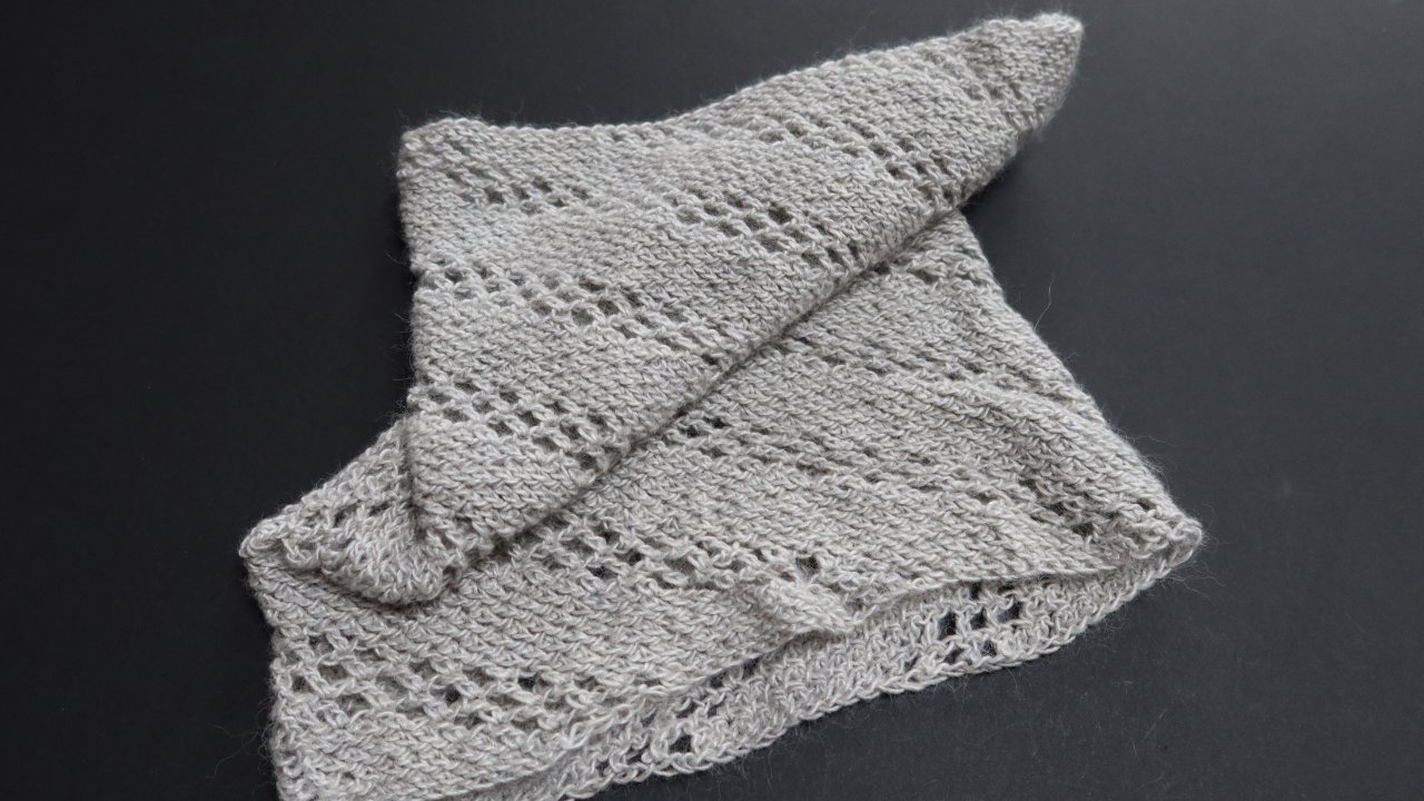 lack background with a silver Positivity Spiral Cowl ploppe don it.  The diagonal lace pattern shows through.