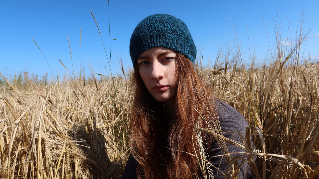 Head shot of my 20 year old brown haired niece wearing a dark teal  Beanie hat which is one of the styles from the Positivity Spiral Hat pattern..