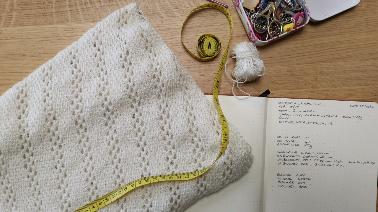 Undyed laceweight version of the Positivity Spiral cowl ona  wooden table with a notebook, yellow measuring tape and notions tin.