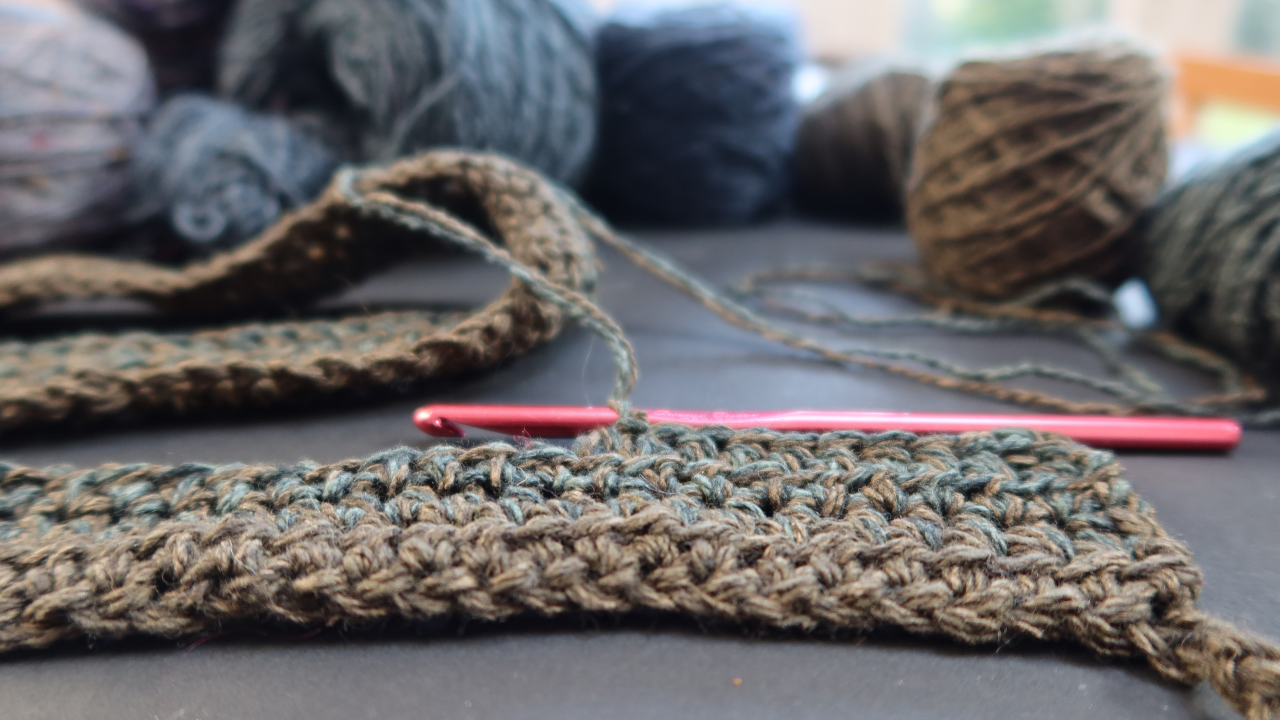 Chunky length of crochet with a red metal crochet hook and scattered cakes of yarn in the background, all in eathy greens and blues.