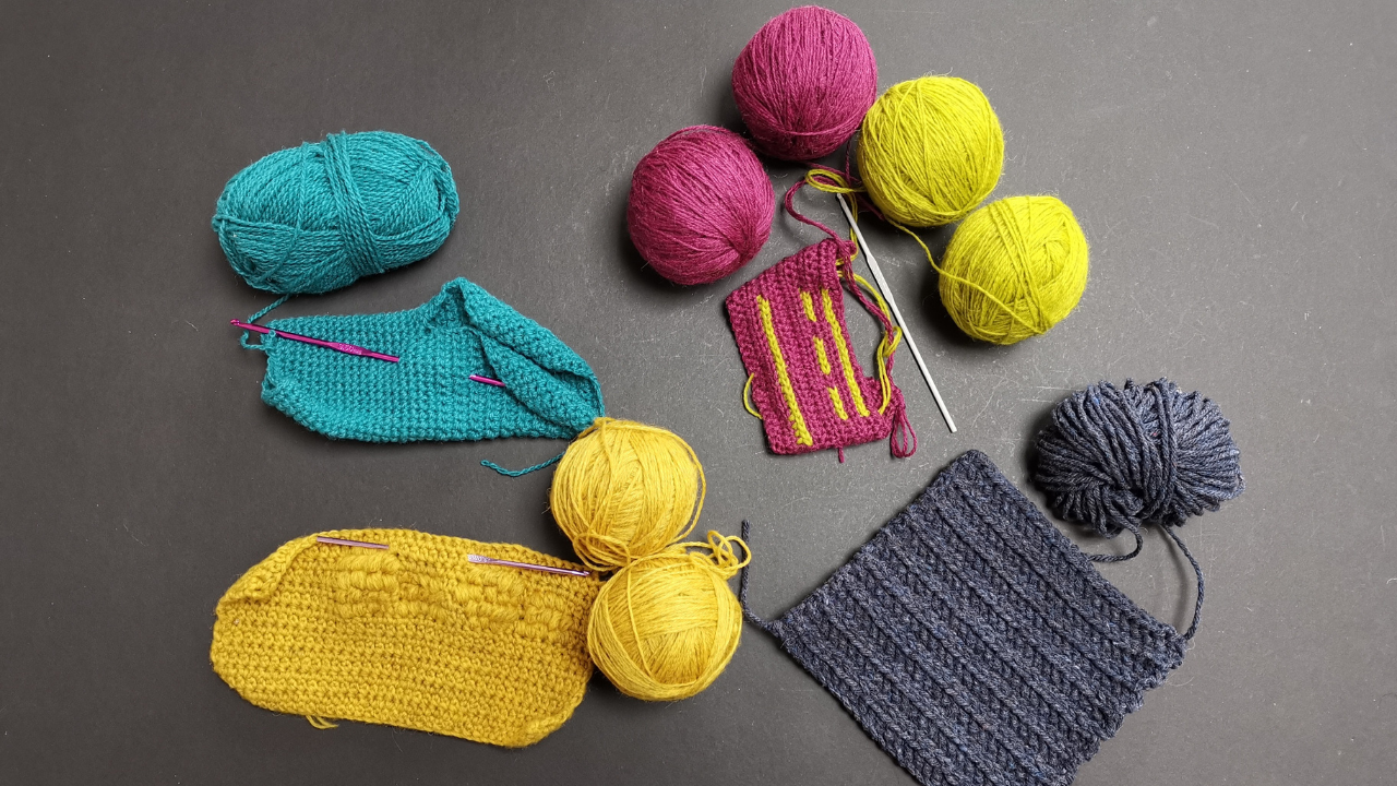 Grey background with four crochet bag swatches in different yarns with hooks.  They yrans range from teal to bright pink and yellow, dark denim blue and honeycomb yellow.