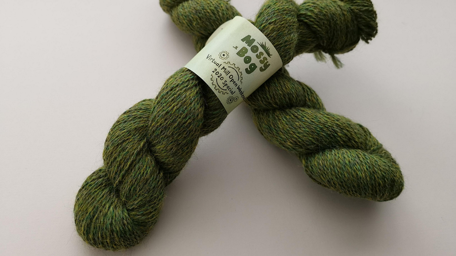 Two skeins of bright green wool. It's very heathered with pops of yellow and dark green.