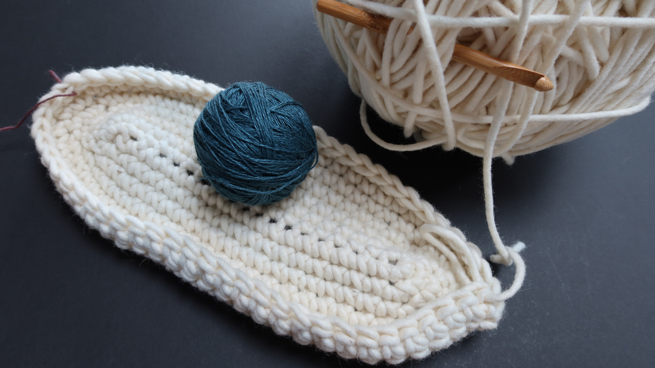 Black background with a huge ball of felted riving wool and a chunky bamboo hook.  The base of a large shopping bag in the same wool  pattern to the front, with a ball of petrol blue linen.
