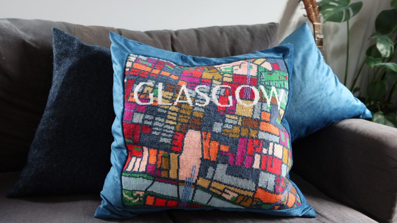 Close up of my grey linen sofa with me made cushions from navy Harris tweed, blue velvet and a Glasgow street map tapestry cushion backed in blue velvet.