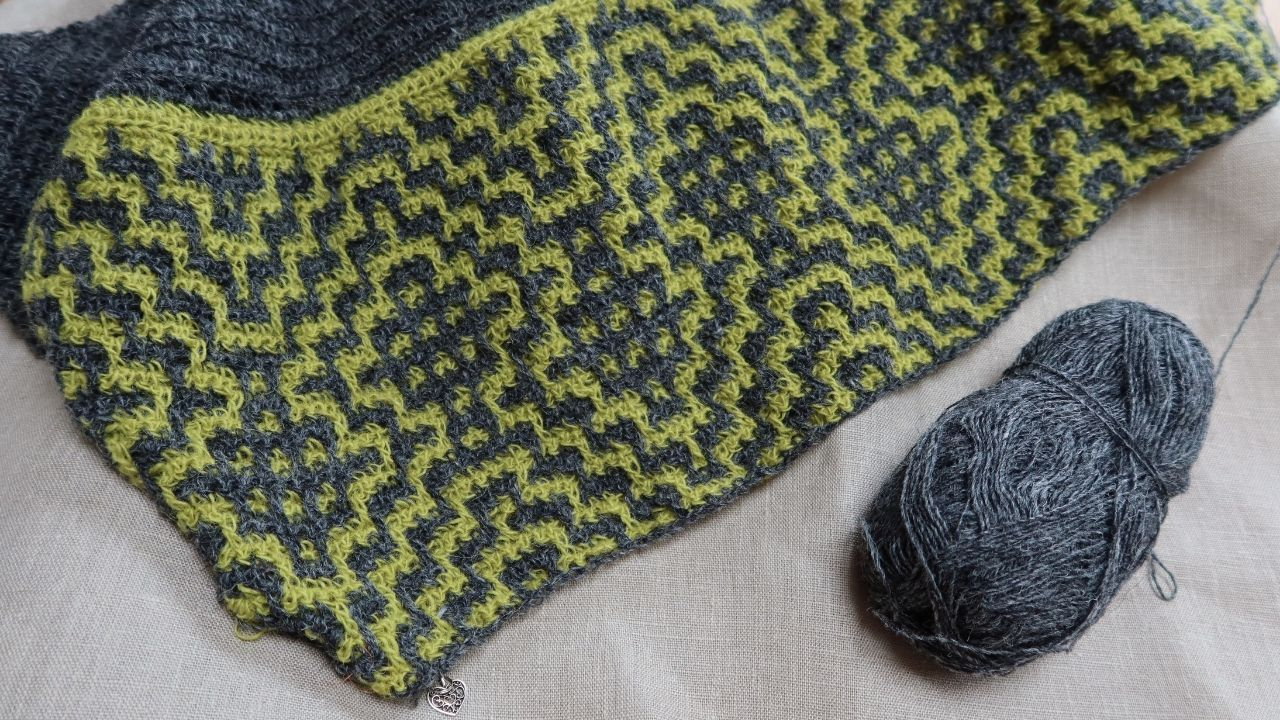 A partially crocheted woollen shawl in charcoal grey and bright yellow.  The mosaic crochet pattern is shown well because of the contrast colours.