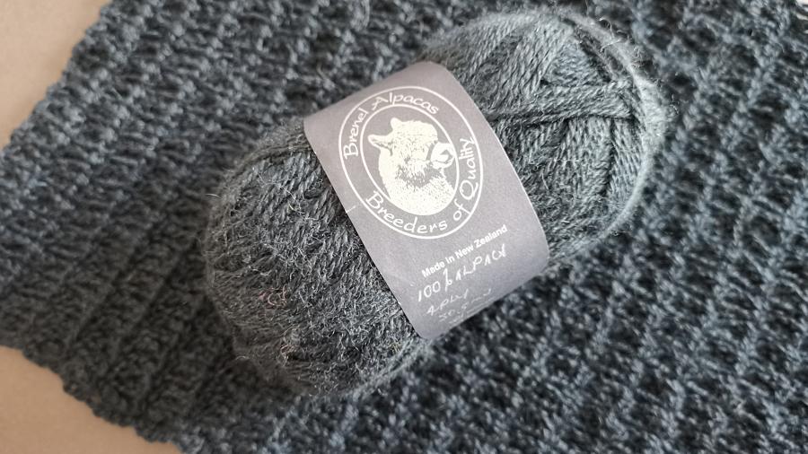 Ball of yarn with a dark ball band for Brenel Alpacas on top offabric crocheted in the same very dark petrol blue/green alpaca yarn.