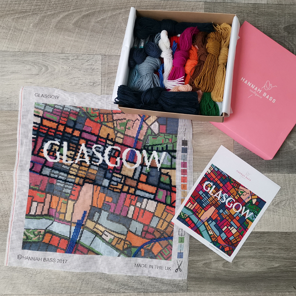"""A tapestry cushion kit with bright wools in a box and a pre-printed canvas of Glasgow's street map and """"Glasgow"""" in text."""