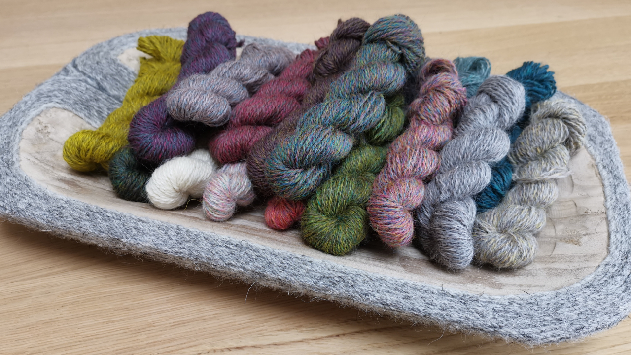 Shallow woodne dish with mini skeins of Appledore wool in 15 shades of grey, pink, ellow, green and brown.