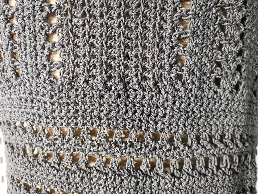 Close up of open work texture of T-shirt top showing horizontal bottom half and vertical top half.