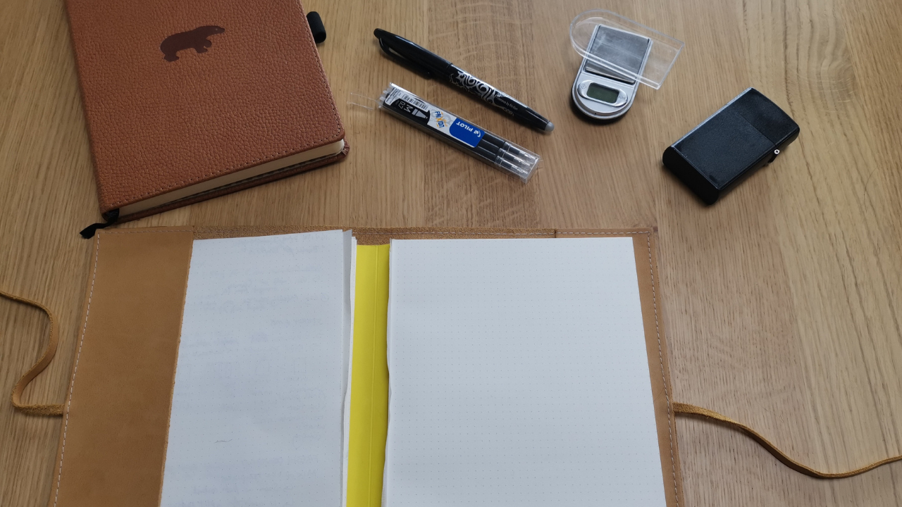 Wooden table with two bound notebooks, one is open.  A pen with refills is a bove it with a set of small jewellery scales and a black case for them.
