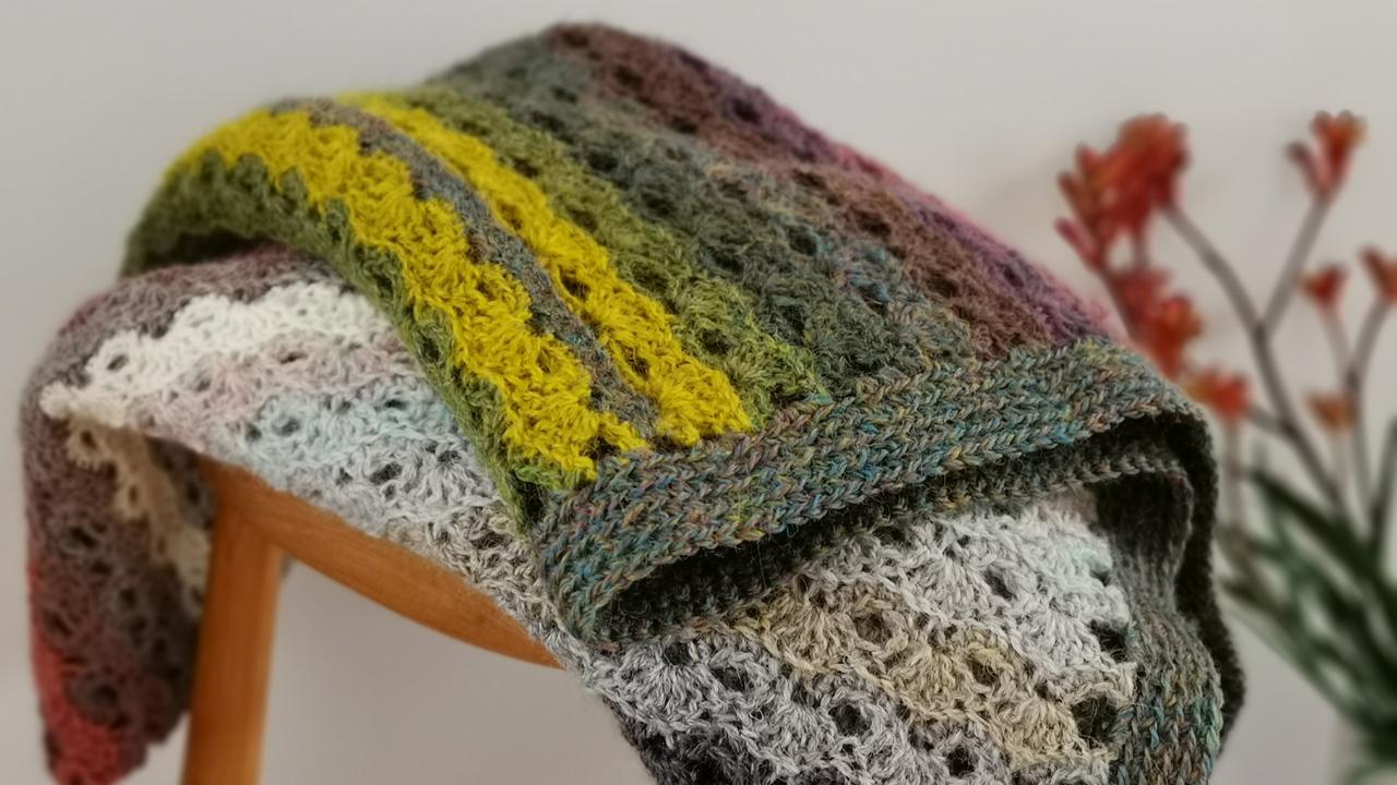 Striped crochet blanket folded on a wooden stool.