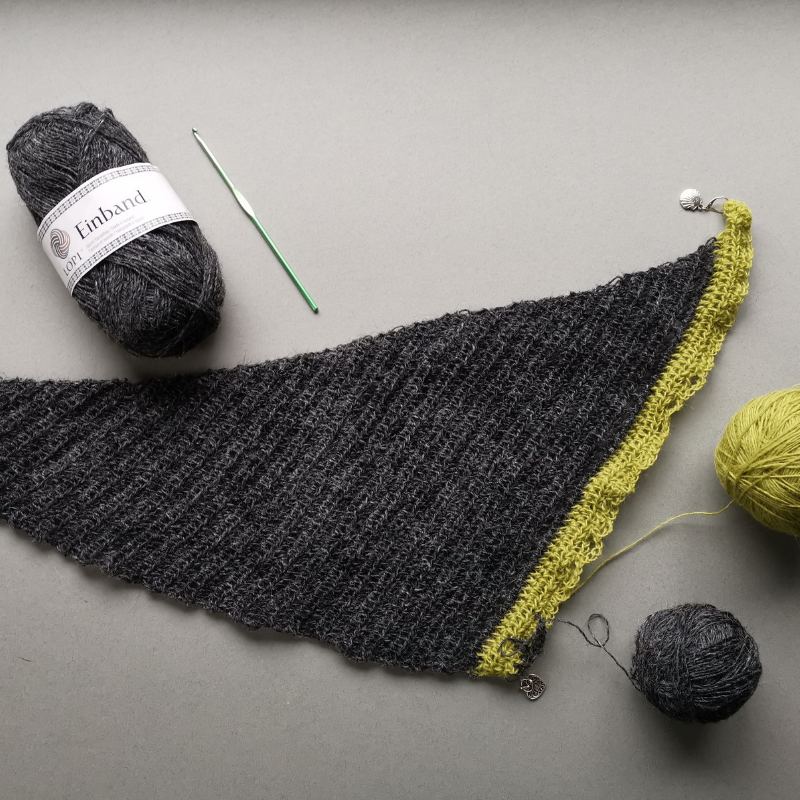 Beginnings of a shawl in charcoal wool with chartreuse wool in the recent rows.