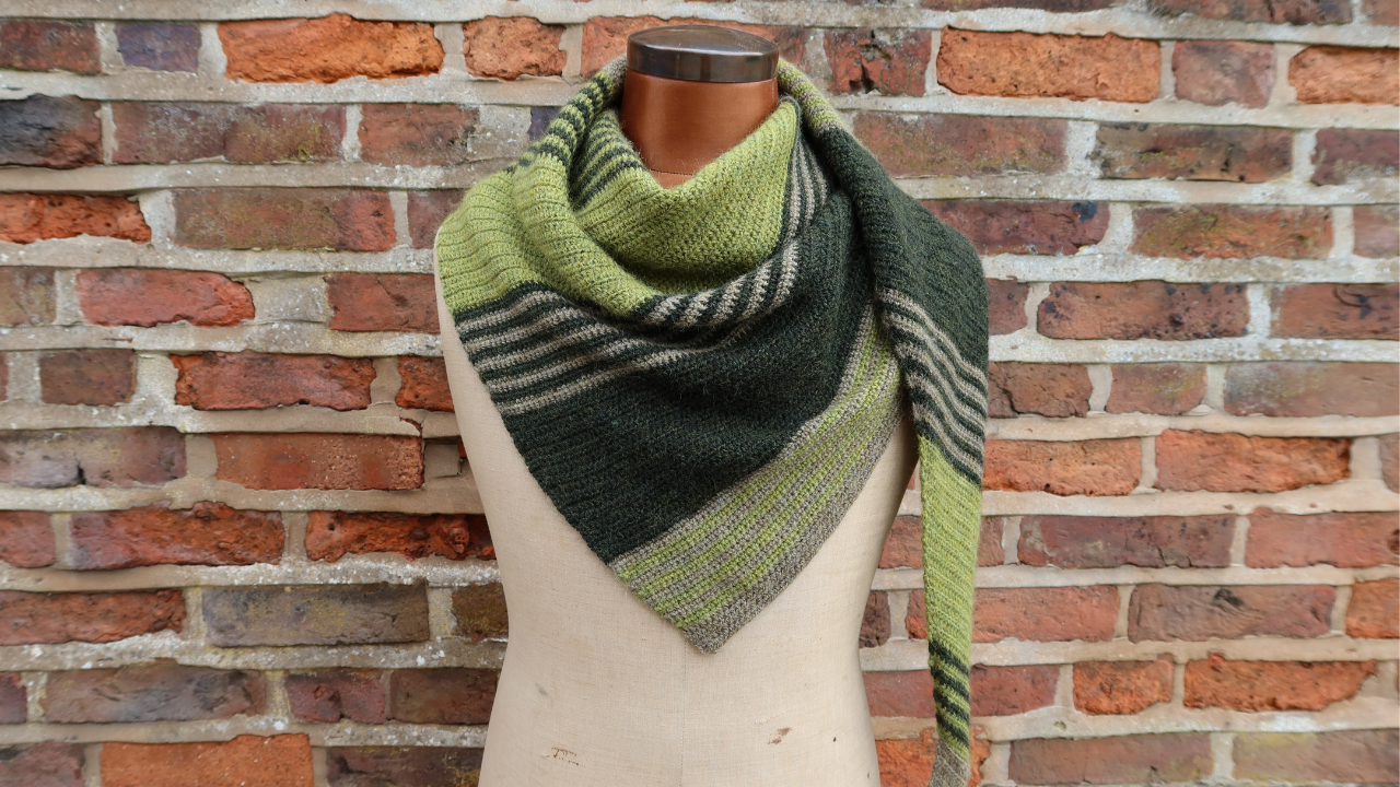 Torso of a mannequin against a red brick wall with a green and fawn striped crocheted shawl on it.