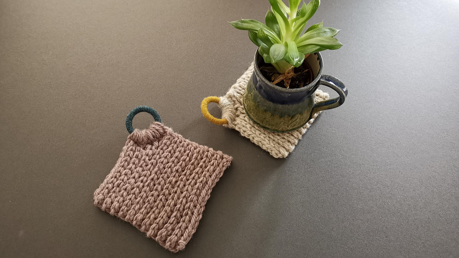 Two woolly coasters with woolly Dorset buttons so that they can hang up.  One coaster has a succulent in a mug on it.