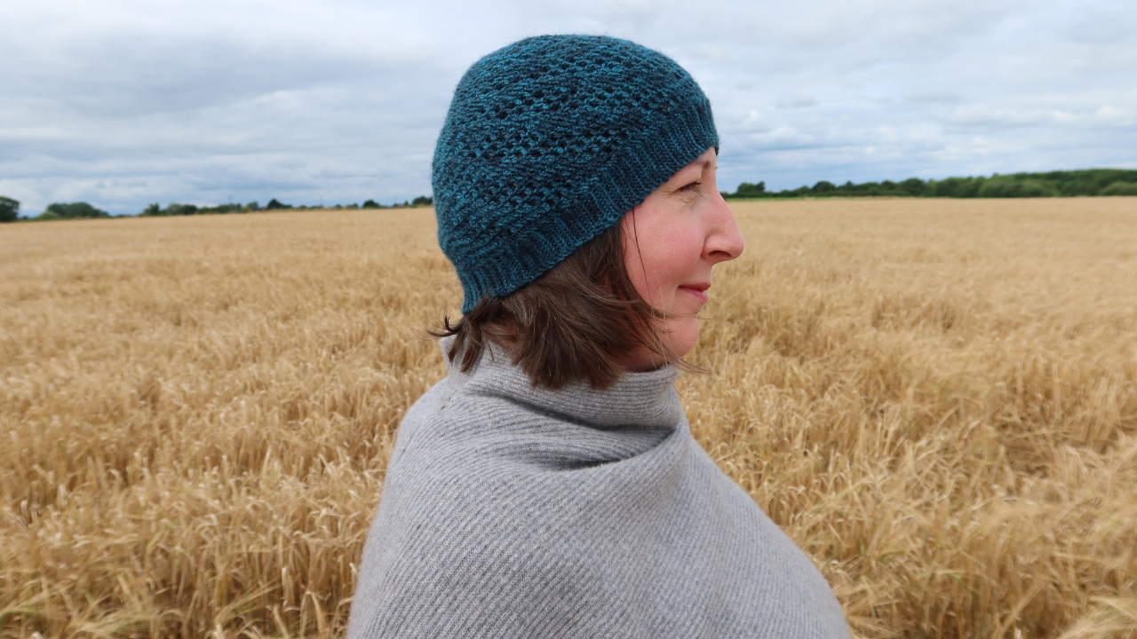 Headshot of me with short brown hair in a cornfield wearing a dark teal  Beanie hat which is one of the styles from the Positivity Spiral Hat pattern..