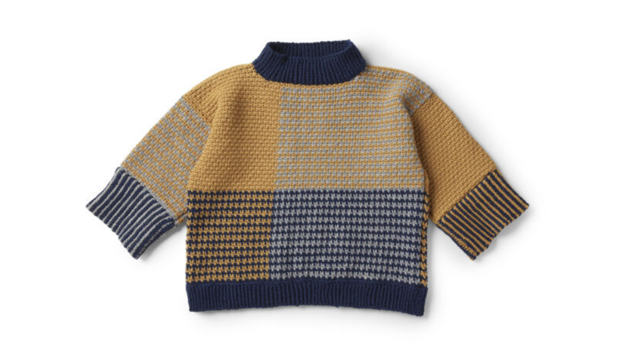 A bold crocheted pullover with navy waist ribbing and collar.  The body and sleeves are in colour blocks with some blocks combing coluors to create a houndstooth effect.