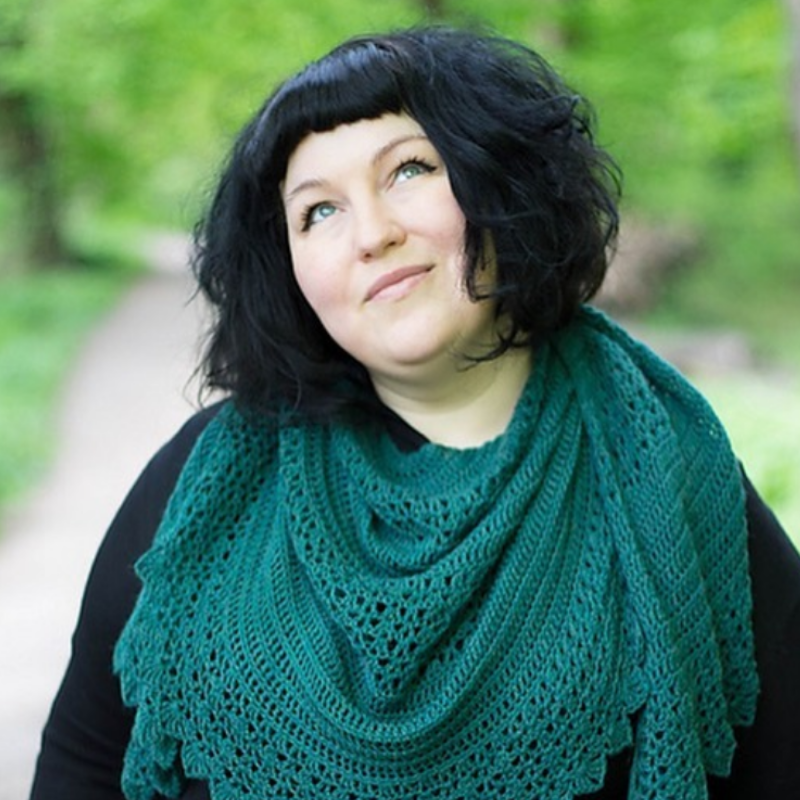 A photo of Anna wearing a black top and green crocheted shawl.  Anna has bobbed black hair and is looking up and smiling.