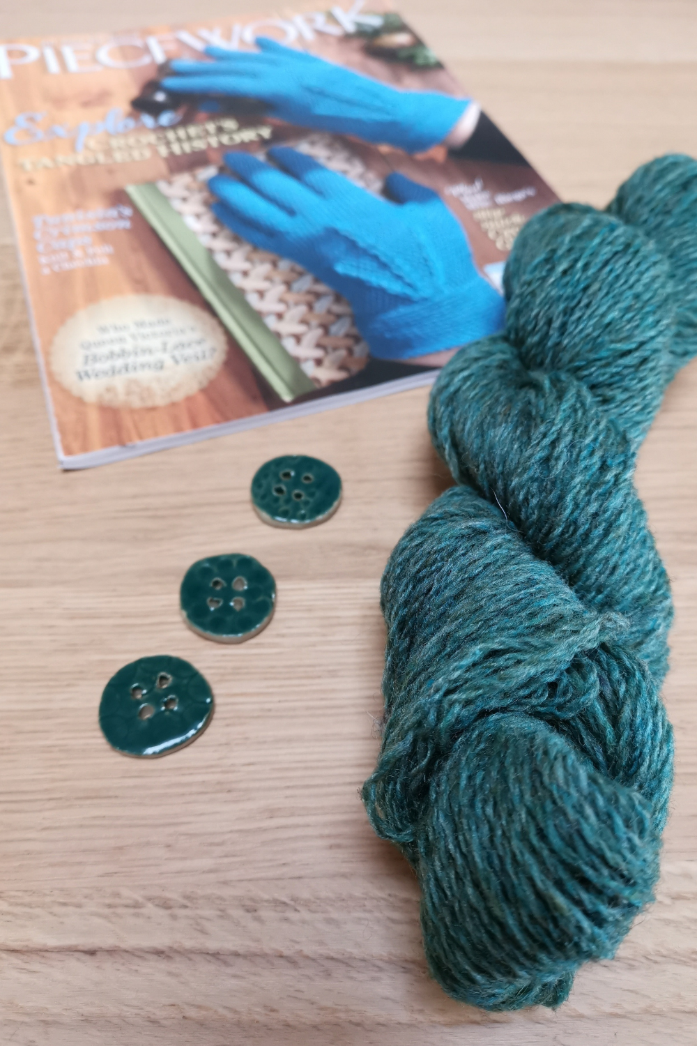 skein of jade green plump wool beside the magazine 'Piecework' and three handmade ceramic buttons in the same jade green.