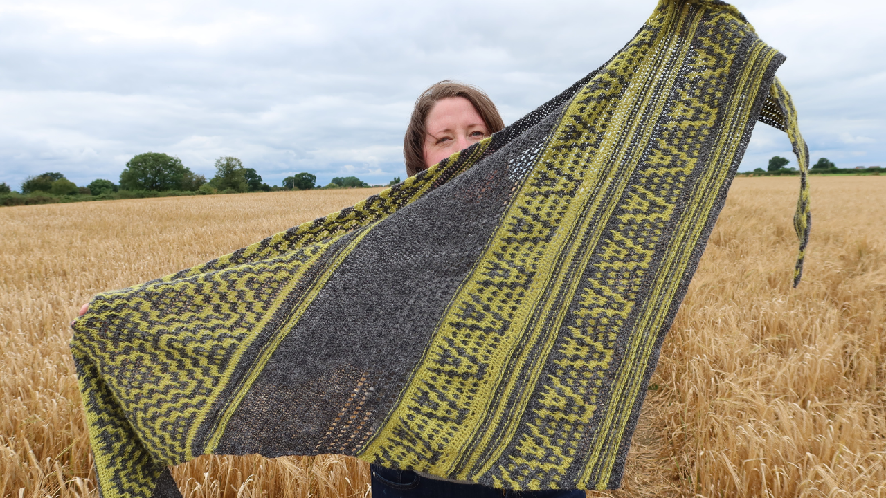 Me stood in a corn field hiding behind my massive crocg=heted Clen Lines shawl which is dark grey and chartreuse.