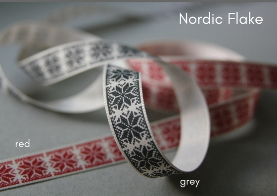 Two looped ribbons with cream backgrounds.  Both have Nordic flake motifs, one on grey and the other in red.