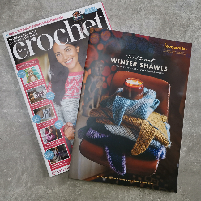Flat lay of Inside Crochet issue 131 and the covermount with my shawls in a pile and a candle on top.