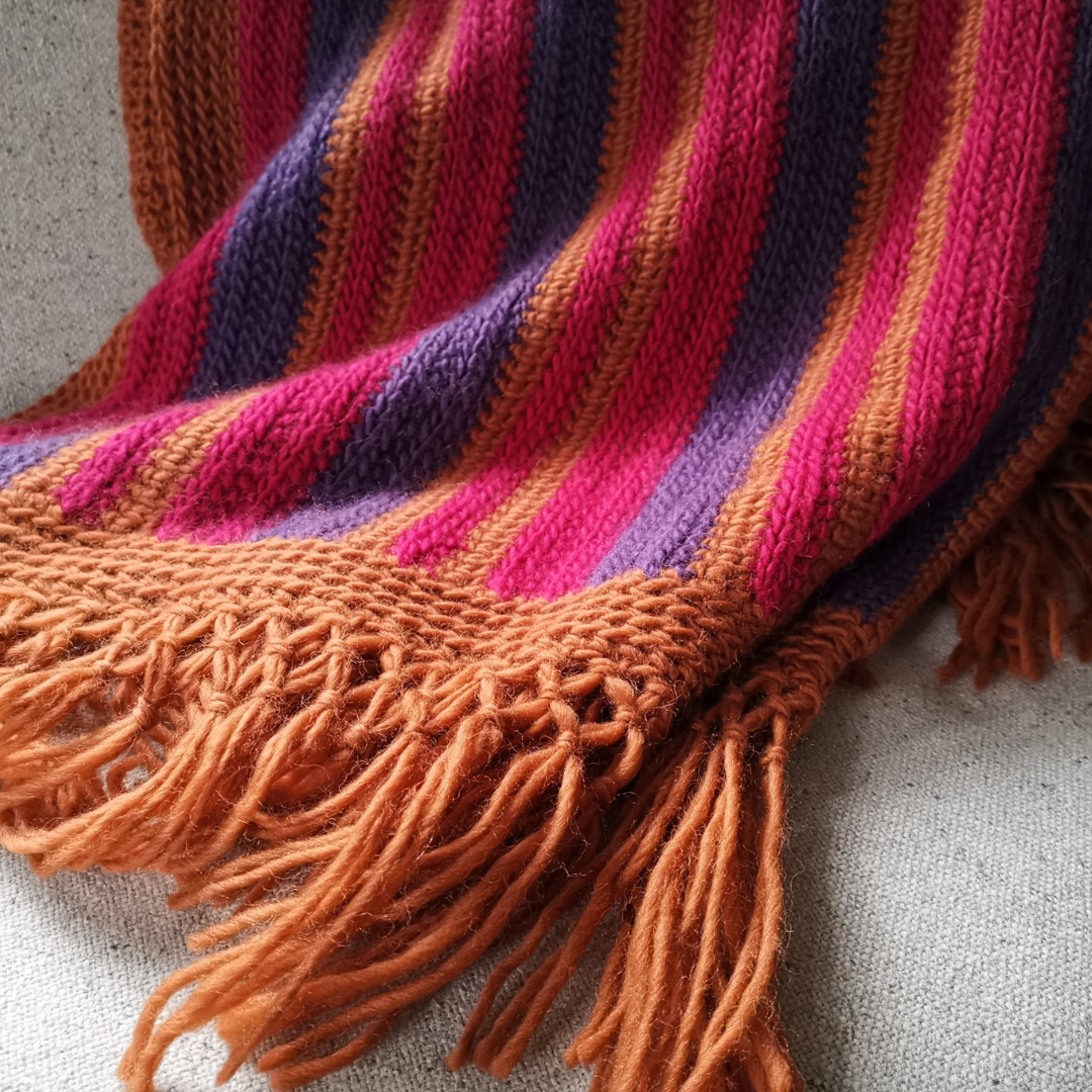 Textured striped crochet blanket in rusty orange, bright raspberry red and deep purple.  The border and macrame fringe are in orange too.