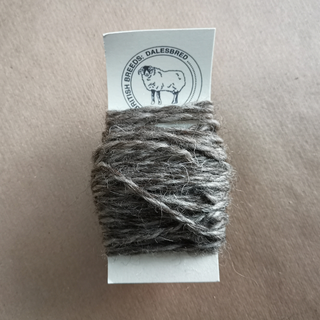 Close up of Dalesbreed wool on its ID tag.  The wool is hand-spun and has a mid brow/grey colouring to it.