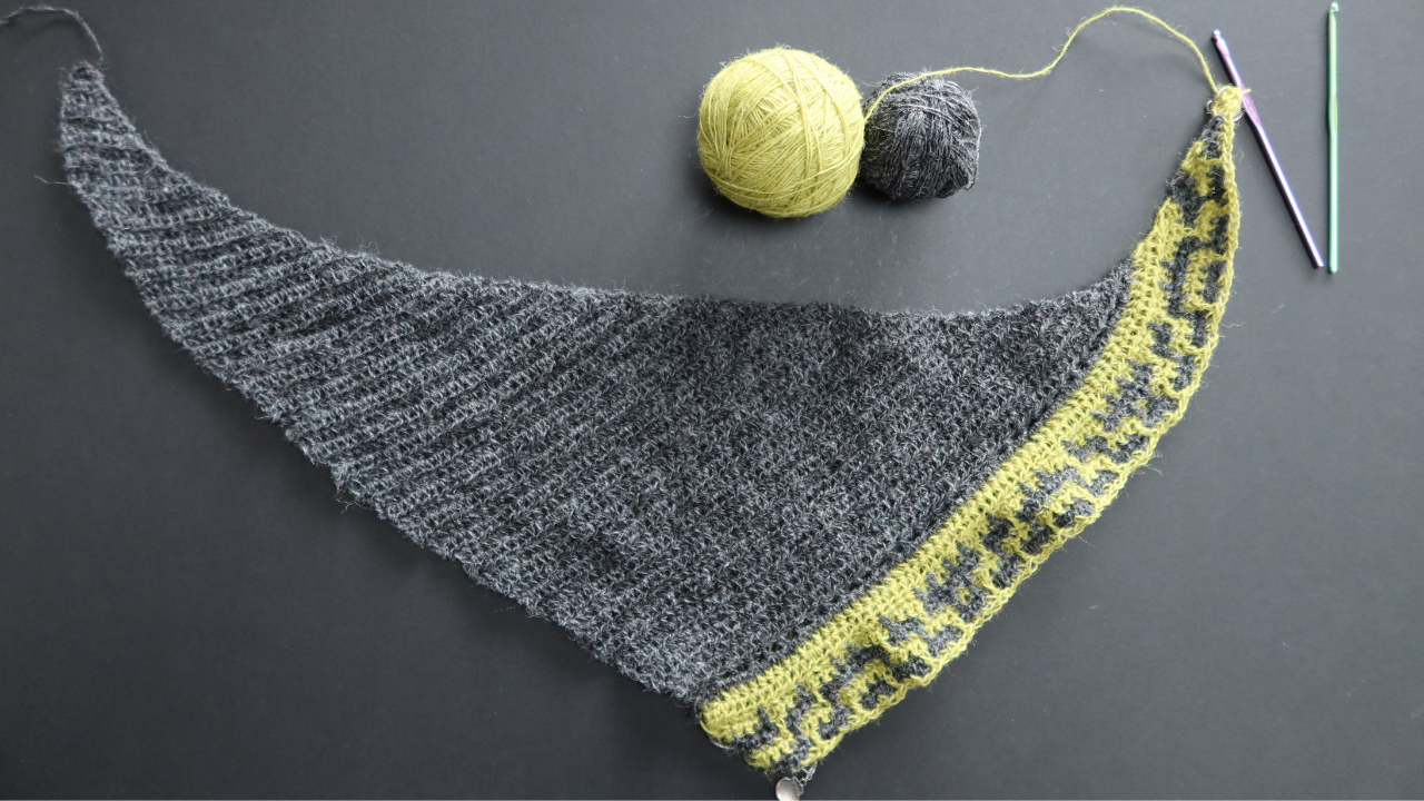 The beginnings of a dark grey wool shawl with a few rows of a zingy ywllo added witht he grey in mosaic crochet.  The balles of wool are in the background with tow metal crochet hooks.