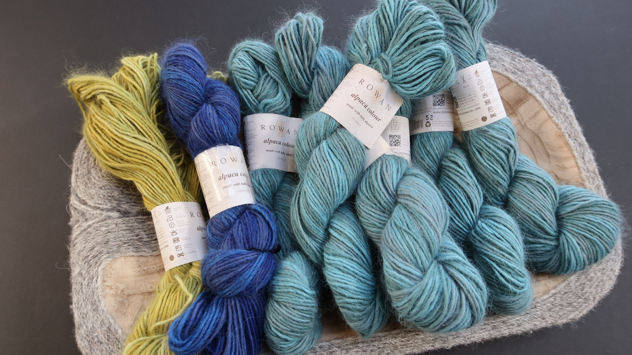 A wooden dish holding skeins of fluffy alpaca yarn in a light teal, dark sky blue and acig green, ready to become a section for th Stitches for Survival banner.