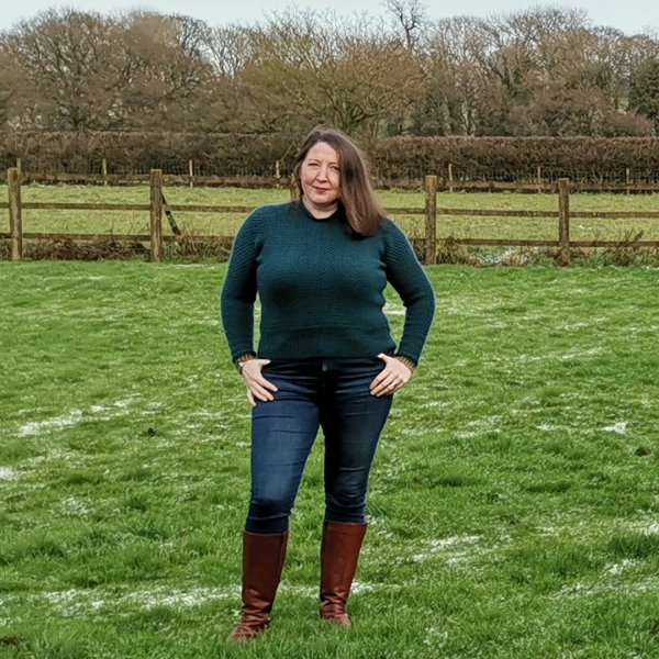 I'm standing in a field with hedgerows behind me, my teal Color Pop sweater on, blue jeans and brown boots.