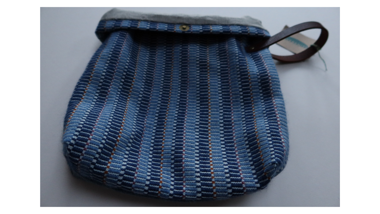 A woven project bag with lozenge shape pattern in dark and mid blue with spots of dusky pink abd orange.  It has a leather handle to the top right.