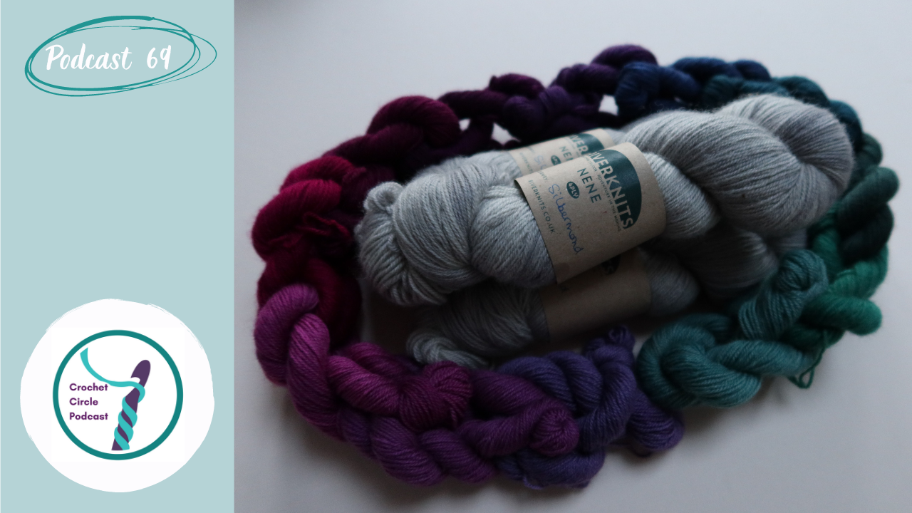 Three skeins of silver wool piled on each other and encircled with 12 mini skeins of wool in vey Scottish colours of purples, teals, blues, pinks and greens.