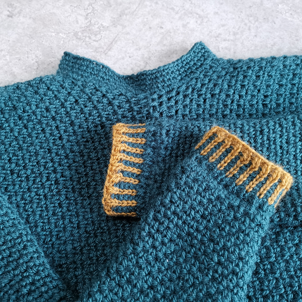 Close up of the knitted sleeve cuff of the Color Pop sweater in mustard and teal.