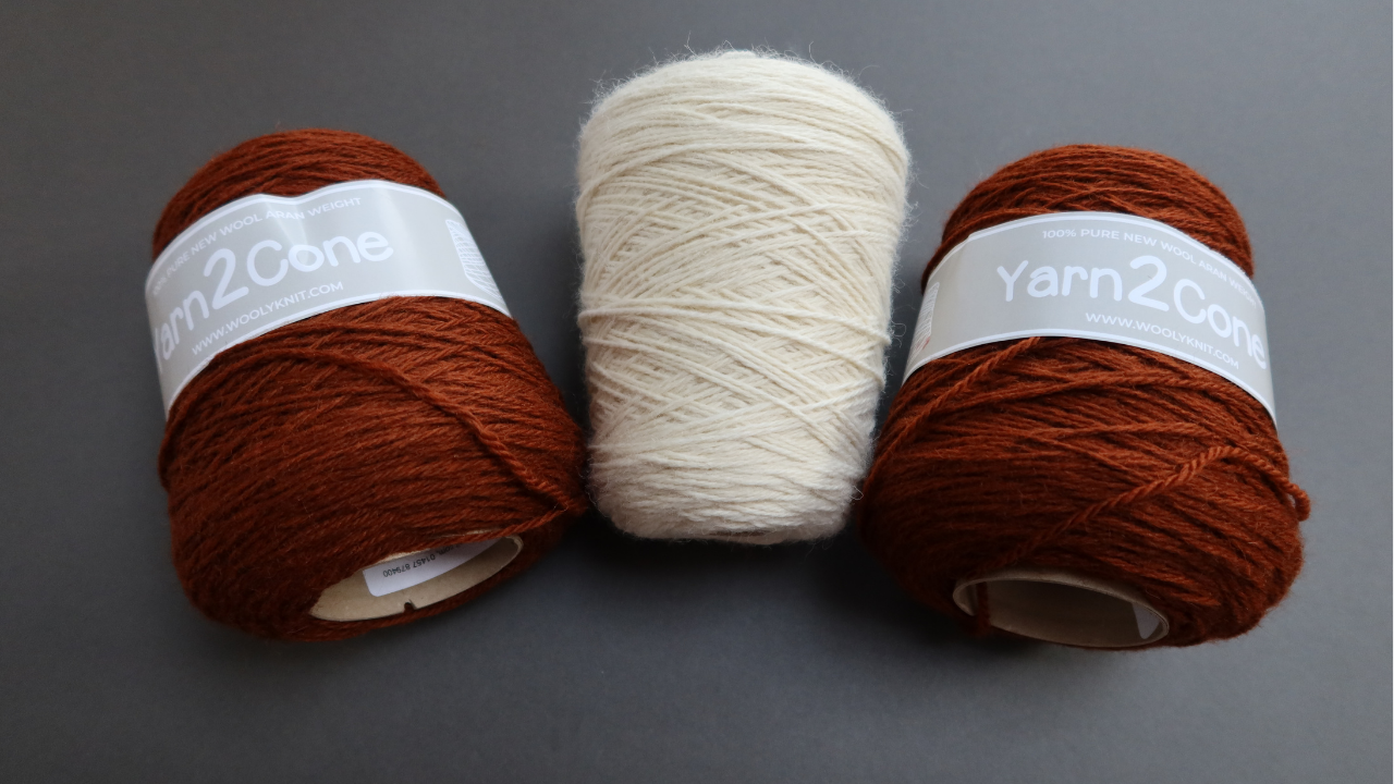 Three cones of aran weight yarn on a grey background.  All are from Woolyknit and teh two outer ones are a dark rust colour and the middle cone id an undyed, bright cream.