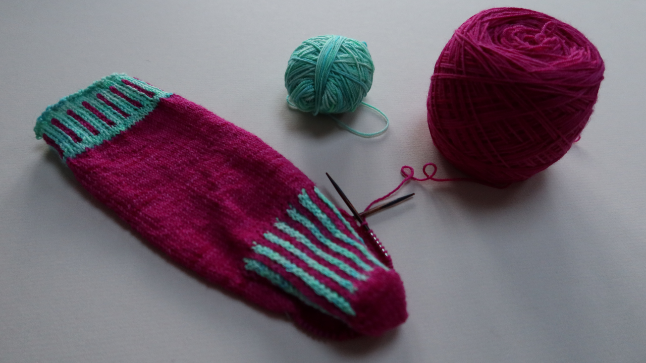 Close up of the cuff, calf and heeel portion of a partially made sock in bright pink, with striped accents using turquoise contrast yarn,