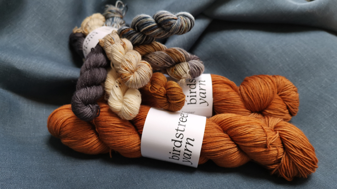 Steel blue linen fabric with skeins of yarn.  Large skeins are rusty orange and teh six mini skeins are in shades of dark grey, mid blues, oatmeals with speckles of rust adn grey.