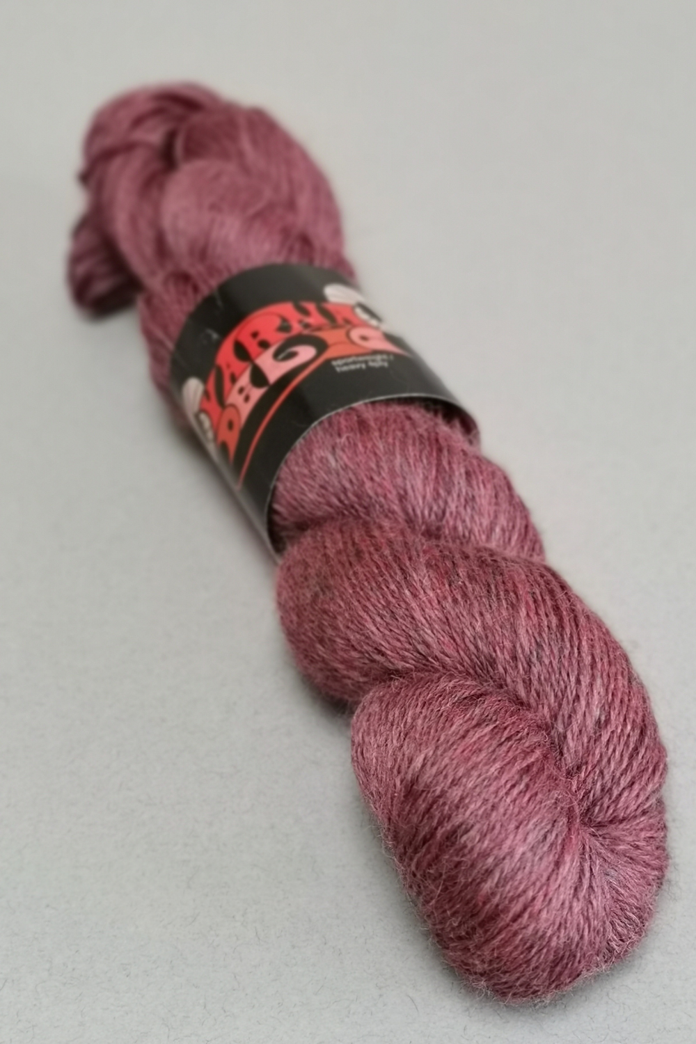Skein of shiny tweed wool in adeep rose pink with hints of blue.  Wool is Yarnadelic from John Arbon Textiles