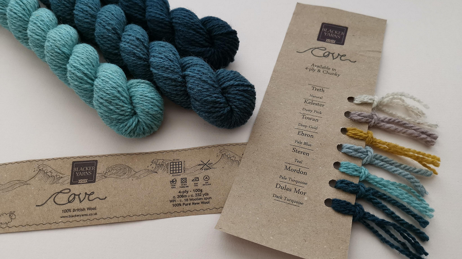 A selection of teal shades in mini skeins with a kraft shade card to the right.  Skeins are plum and woolly and Cove from Blacker Yarns