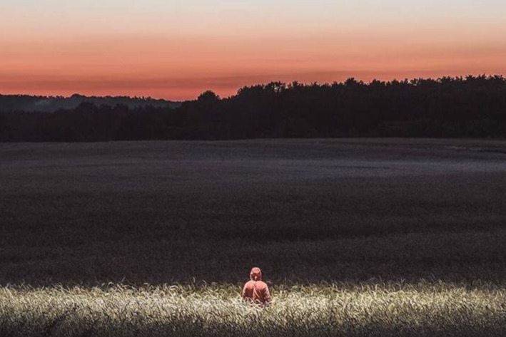 person sitting in field at sunset