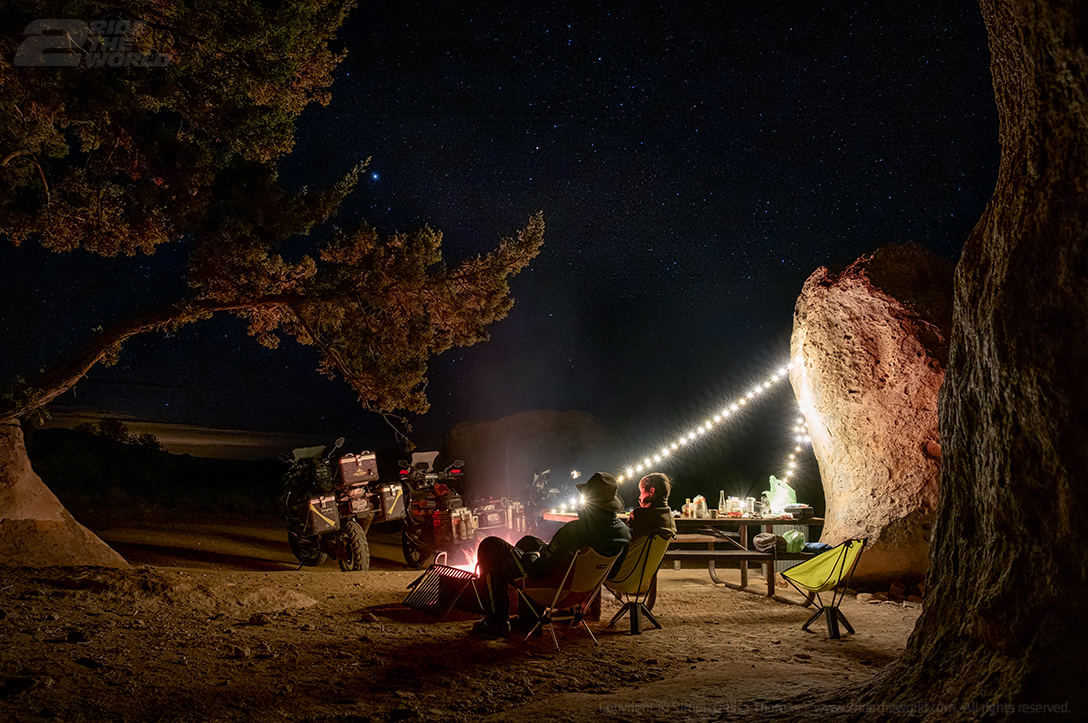 two people sitting in chairs at campsite under the night sky