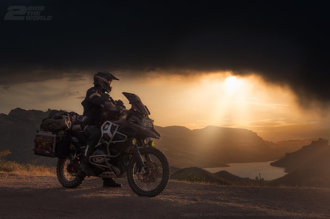 person on dirt bike overlooking view of desert