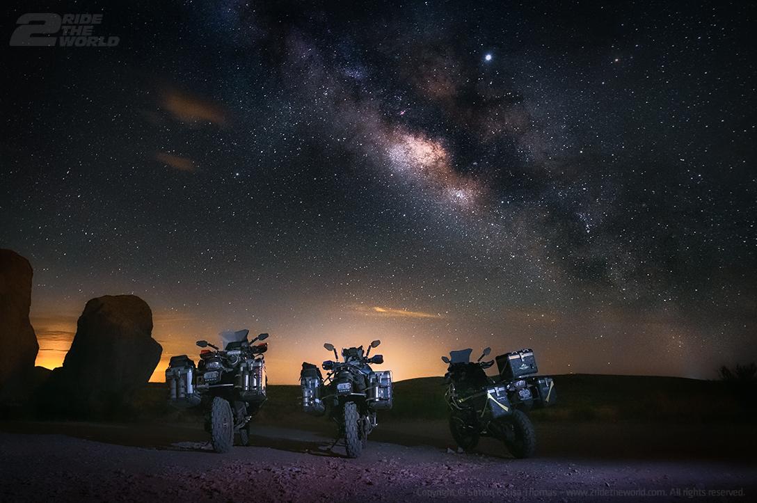 three dirt bikes under the starry night sky