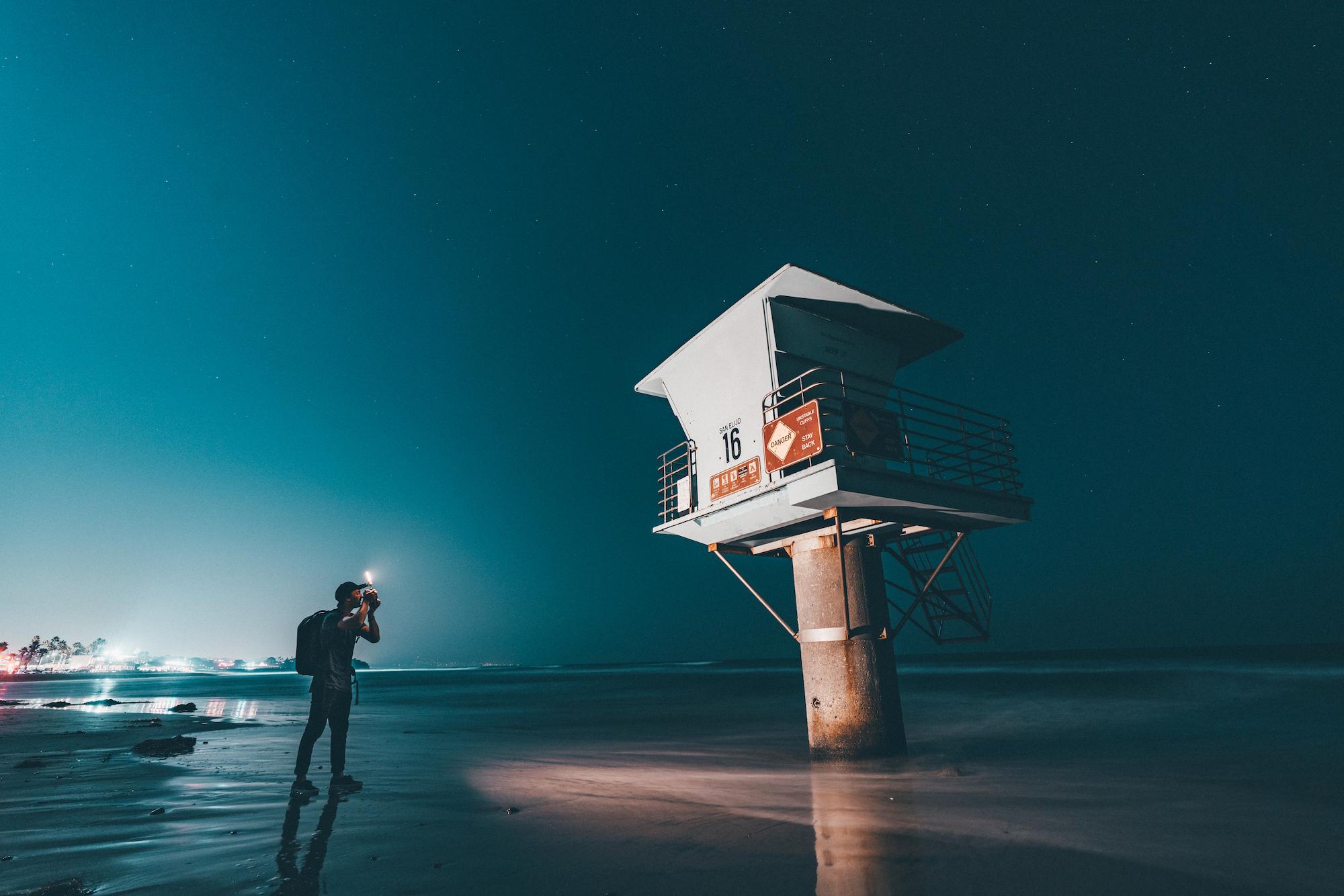 man taking photo at night of lifeguard tower at beach using panel pro