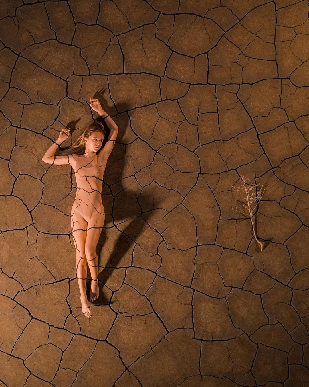 woman laying on dry and cracked dirt