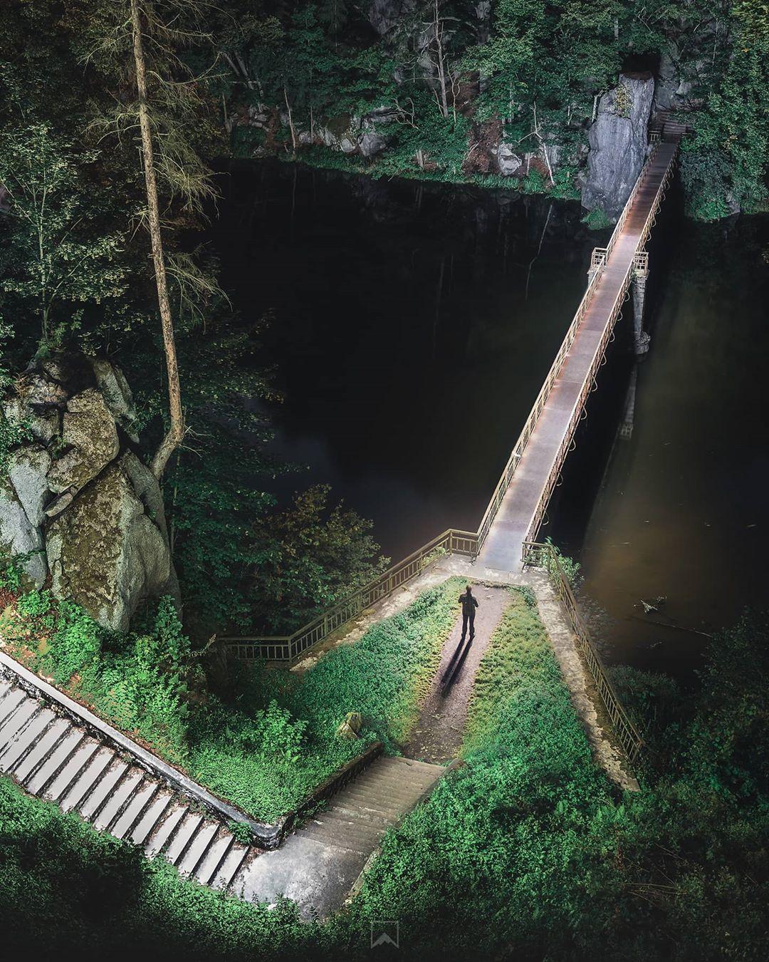 man standing before long bridge overlooking water